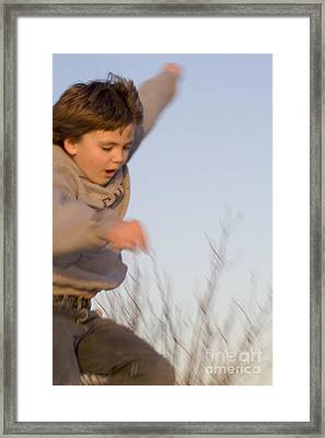 Boy Jumping Off Sand Dune Framed Print by Christopher Purcell
