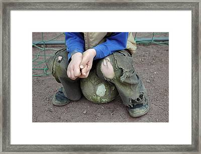 Boy Sitting On Ball - Torn Trousers Framed Print by Matthias Hauser