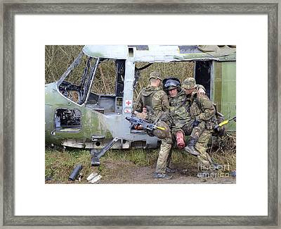 British Soldiers Help A Simulated Framed Print by Andrew Chittock
