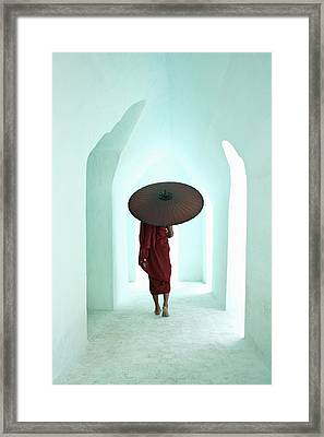 Buddhist Monk Walking Along Arched Temple Corridor Framed Print by Martin Puddy