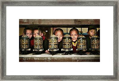 Buddhist Monks In Red Robes Look Out Of The Prayer Wheels With M Framed Print by Max Drukpa