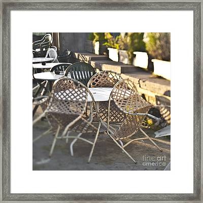 Chairs Leaning Up Against A Table Framed Print by Eddy Joaquim