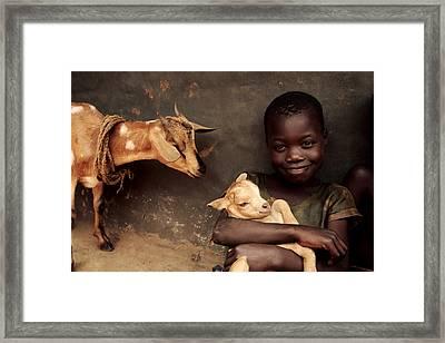 Child Holding A Kid Framed Print by Mauro Fermariello