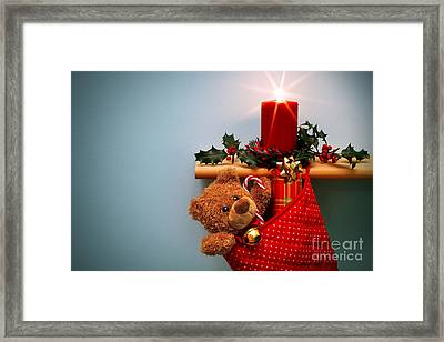 Christmas Stocking Filled With Presents With Candle And Holly. Framed Print by Richard Thomas