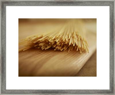Close Up Of Uncooked Spaghetti Noodles On Cutting Board Framed Print by Adam Gault