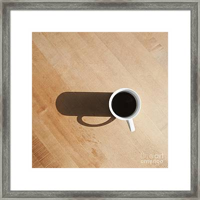 Coffee Cup And Shadow On A Table Framed Print by Jetta Productions, Inc