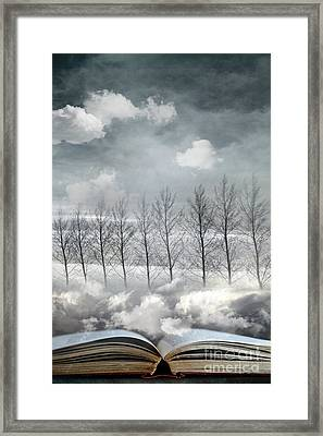 Conceptual Image Of Open Book With Floating Clouds And Trees Framed Print