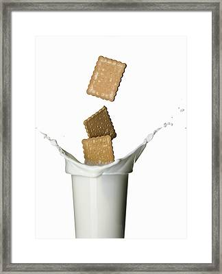 Cookies Splashing Into Glass Of Milk Framed Print by Walter Zerla