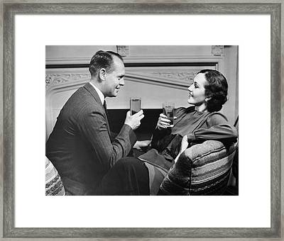 Couple On Couch Having Drinks Framed Print by George Marks