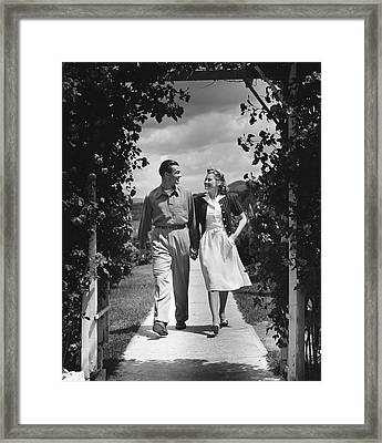Couple Outdoors Holding Hands While Walking Framed Print by George Marks