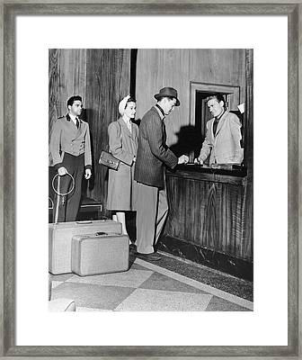 Couple Signing In At Hotel Lobby Framed Print by George Marks