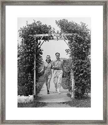 Couple Walking On Footpath Towards Rose Covered Pergola, (b&w) Framed Print by George Marks