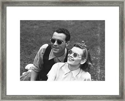 Couple Wearing Sunglasses Sitting On Grass, (b&w) Framed Print by George Marks