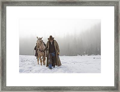Cowboy Walking His Horse And Holding A Shotgun Framed Print by Thomas Kokta