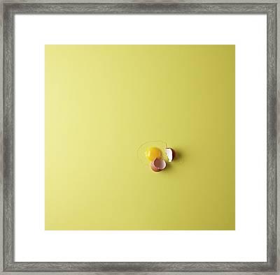 Cracked Egg On Yellow Background Framed Print