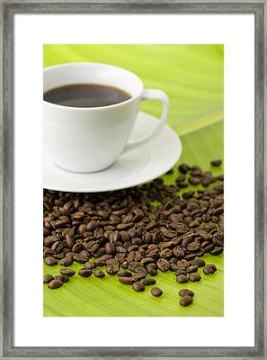 Cup Of Coffee And Coffee Beans On Green Leaf Framed Print by Claudia Uribe
