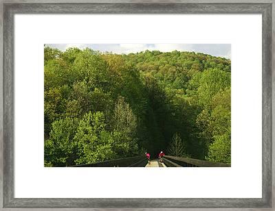 Cyclists Cross A Bridge Framed Print by Joel Sartore