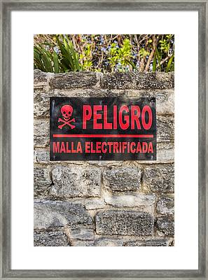 Danger Sign In Spanish On A Stone Wall Framed Print
