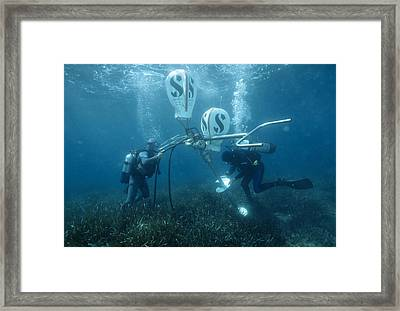 Divers Fixing A Buoy Framed Print by Alexis Rosenfeld