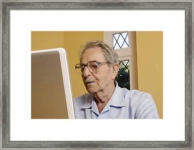 Elderly Man Using A Laptop Computer Framed Print by Steve Horrell