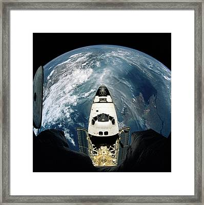 Elevated View Of A Spacecraft Orbiting Over The Earth Framed Print by Stockbyte