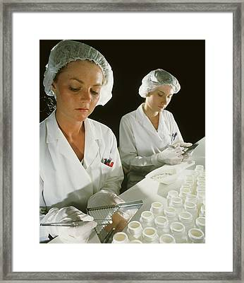 Female Technicians Counting Pills Into A Bottle Framed Print by Geoff Tompkinson