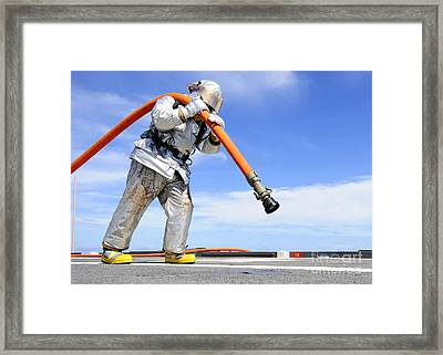 Firefighter Carries A Charged Hose Framed Print by Stocktrek Images