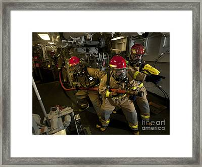 Firemen Combat A Simulated Fire Aboard Framed Print by Stocktrek Images