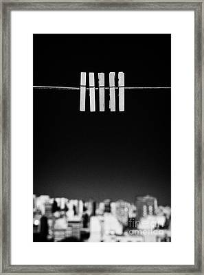 Five Clothespegs Close Up Hanging On A Washing Line With Blue Sky Above City Skyline Framed Print by Joe Fox