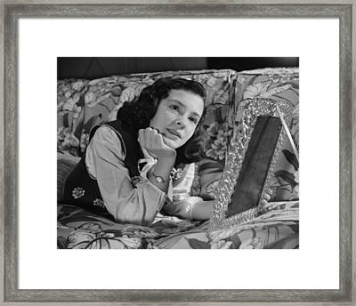 Girl (8-9) Lying On Couch, Holding Framed Photo , (b&w) Framed Print by George Marks