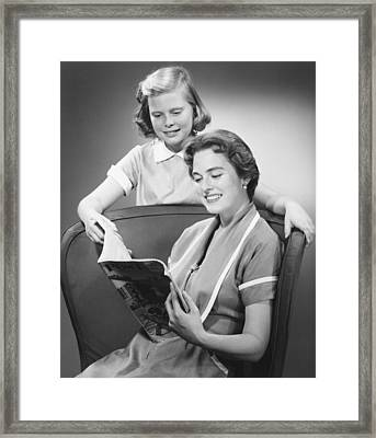 Girl (8-9) Standing At Mother Reading Magazine, (b&w) Framed Print