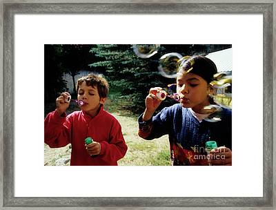 Girl And Boy Blowing Bubble-wands Framed Print by Sami Sarkis