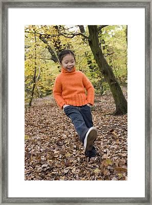 Girl Kicking Leaves Framed Print by Ian Boddy