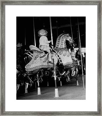 Girl Riding A Carousel Framed Print by George Marks