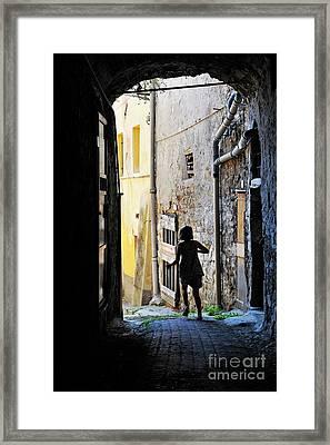 Girl Running Through A Cobblestone Street Framed Print by Sami Sarkis
