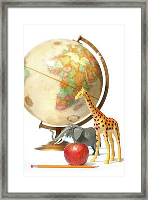 Globe With Toys Animals On White Framed Print by Sandra Cunningham