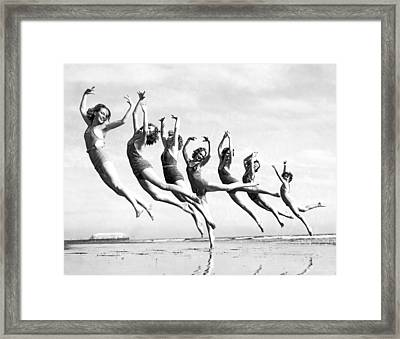 Graceful Line Of Beach Dancers Framed Print by Underwood Archives