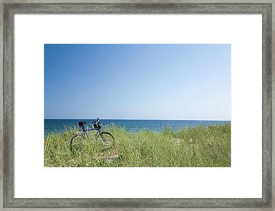 Grass Covering Bicycle Parked On Beach Dune. Framed Print by Alberto Coto