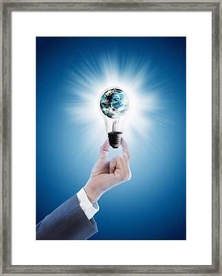 Hand Holding Light Bulb With Globe  Framed Print