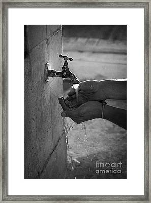 Hispanic Man Cupping Water And Washing Hands At Outdoor Tap Framed Print