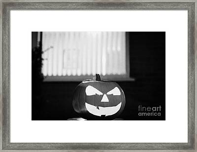 Illuminated Halloween Pumpkin Jack-o-lantern Outside The Window Of A House To Ward Off Evil Spirits  Framed Print by Joe Fox
