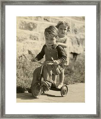 Little Boy Giving Little Girl Ride On Tricycle Framed Print by George Marks