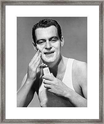 Man Applying Lotion Framed Print by George Marks
