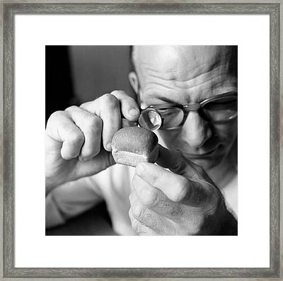 Man Looking At Miniture Loaf Of Bread Through Magnifying Glass Framed Print by Hulton Archive
