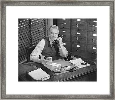 Man Sitting At Desk, Talking On Phone, (b&w), Elevated View Framed Print by George Marks