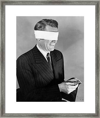 Man Wearing Blindfold Holding Money (b&w) Framed Print by Hulton Archive