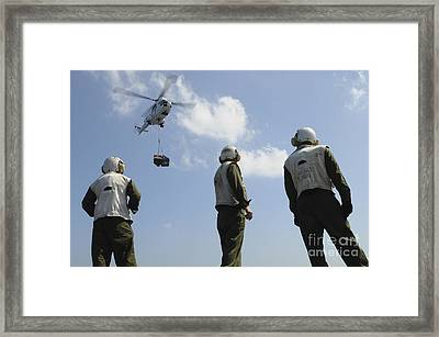 Marines Wait To Retrieve A Pallet Framed Print by Stocktrek Images