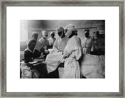 Masked Surgeons Perform An Operation Framed Print by Everett