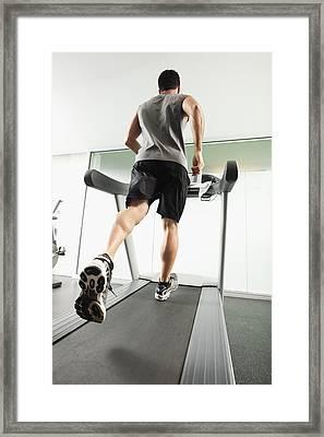 Mixed Race Man Running On Treadmill Framed Print by Erik Isakson