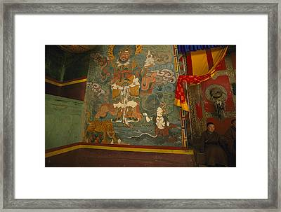 Monks Sit Outside A Buddhist Temple Framed Print by David Edwards